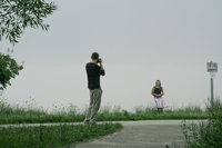 Boy photographing girlfriend on foggy day.